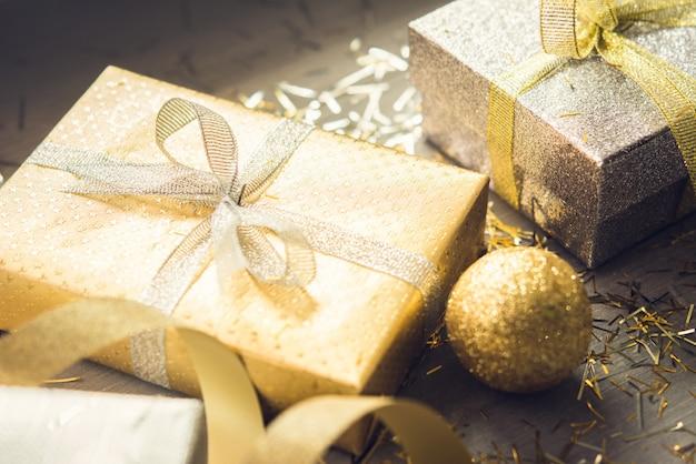 나무 테이블에 은색과 금색 쉬머 크리스마스 선물 상자 프리미엄 사진