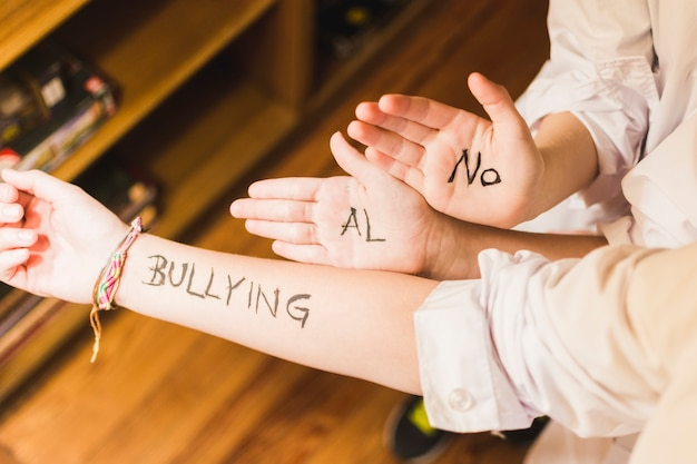Slogan against bullying written on children's hands Premium Photo