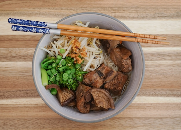 Slow cooked pork spare noodles with shiitake mushroom and mixed vegetables or braised pork noodle soup. Premium Photo