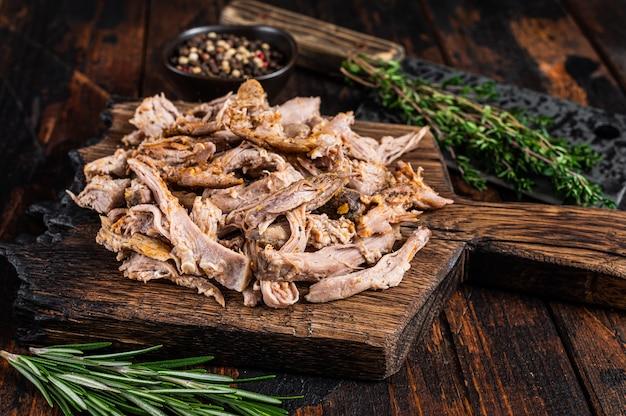 Свинина, приготовленная на медленном огне на деревянной доске с ножом для мясника. темное дерево Premium Фотографии