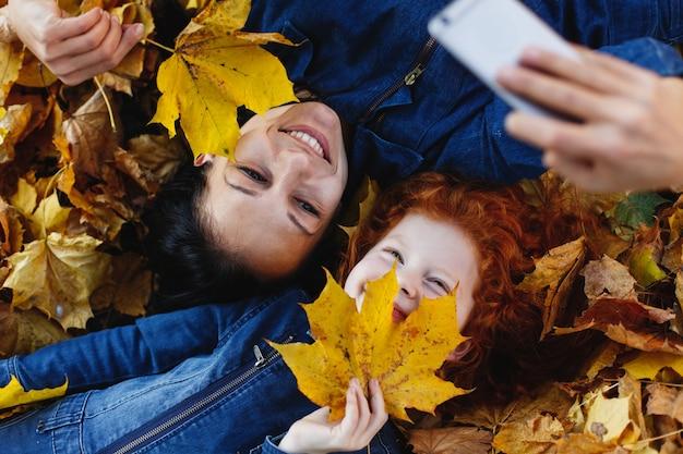秋の雰囲気、家族の肖像画。魅力的なママと彼女の赤い髪の娘はsmにselfieを取って楽しんでいます 無料写真