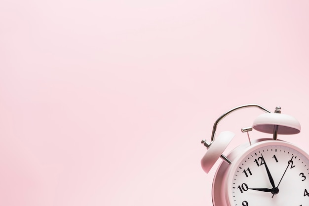 Small alarm clock on the corner of the pink background Free Photo