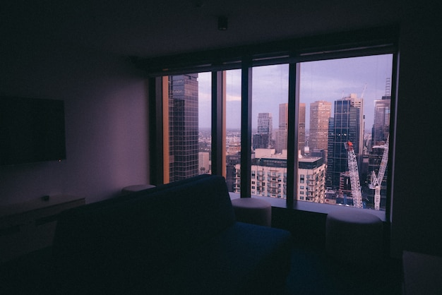 都市建築を望む大きな窓のある小さなアパート 無料写真