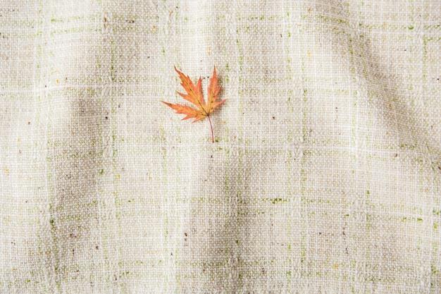 Небольшой осенний лист. плоская планировка. скатерть фон. минималистичный стиль. Premium Фотографии