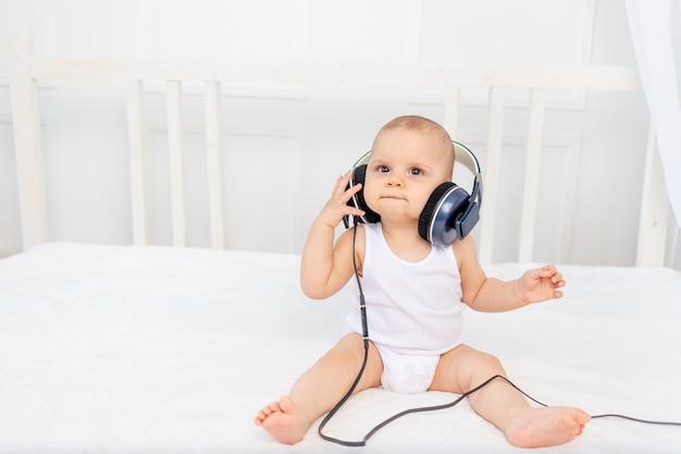 Маленький мальчик 8 месяцев сидит на кровати в детской комнате с наушниками и слушает музыку Premium Фотографии