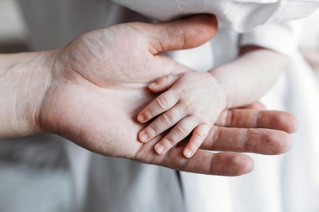 Маленькая детская рука ребенка в руке матери Premium Фотографии