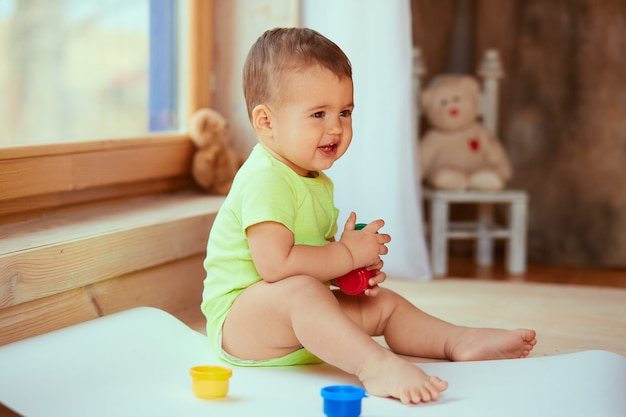 The small baby keeps a box with paints Free Photo