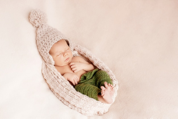 Small baby tucked in a woolen cap Premium Photo
