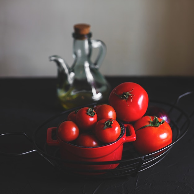 Small and big ripe tomatoes in steel vase and red ceramic pot Free Photo