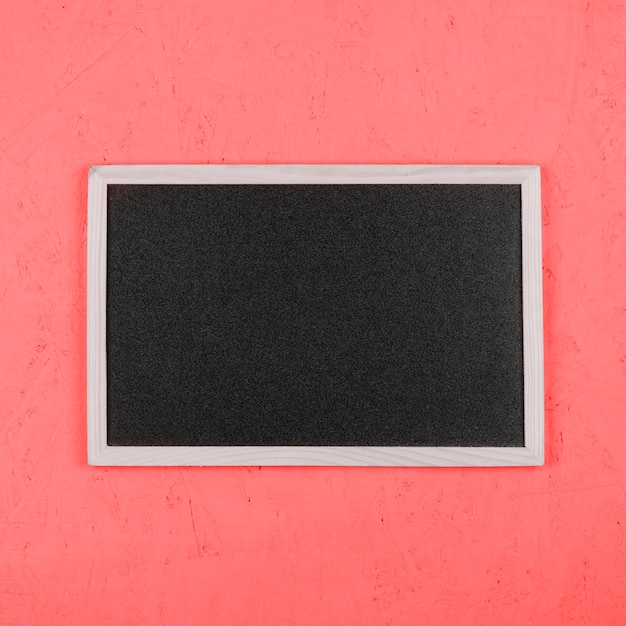 Small blank blackboard on coral painted wall Free Photo