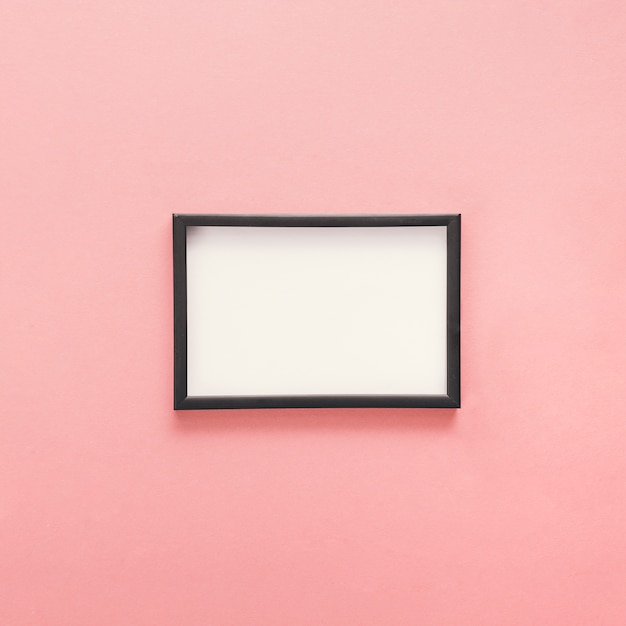 Small blank frame on pink table Premium Photo
