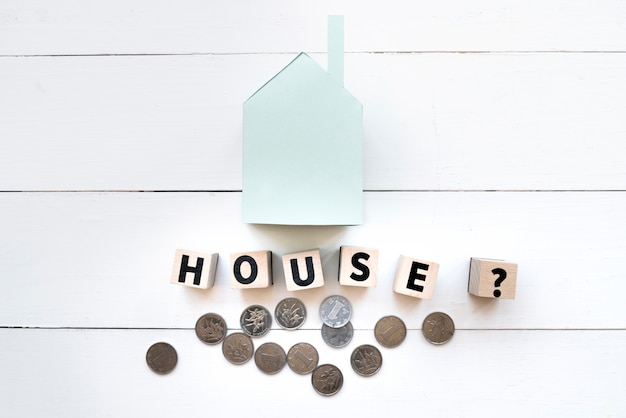 Small blue paper house model with letter wooden blocks and coins on white wooden table Free Photo