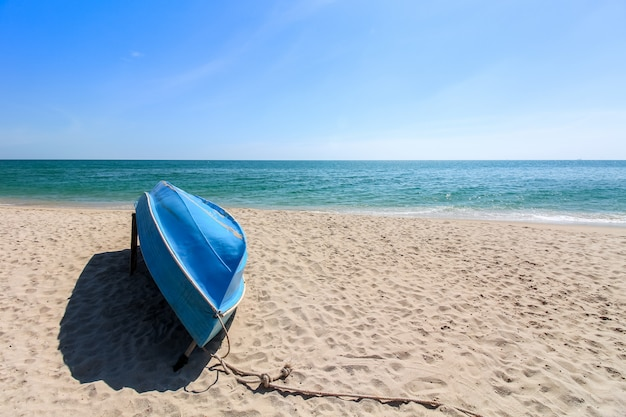 Small blue sailing boat upside down lays on the beach Premium Photo