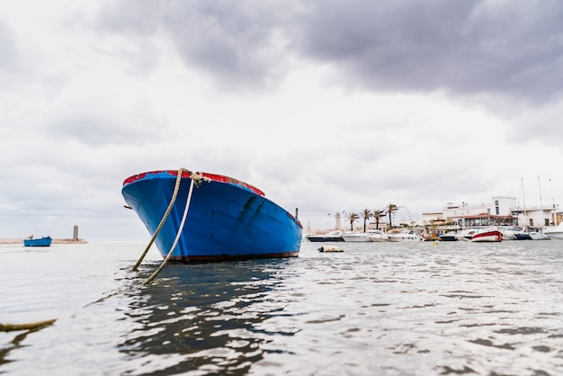 Small boat moored to bari port, italy, during a storm at sea