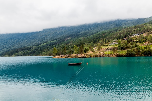 Small boat moored on blue calm lake with green mountain Free Photo