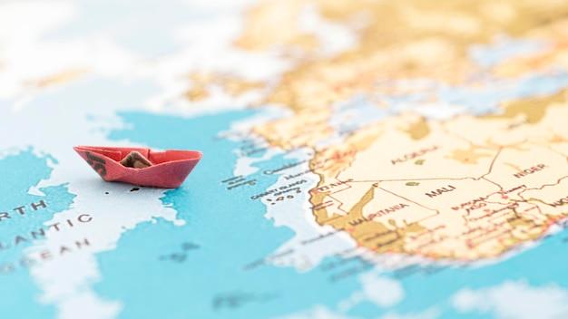Маленькая лодка на карте мира высоким углом Premium Фотографии