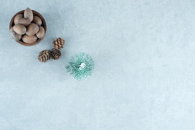 Ciotola piccola di mandorle, pigne e una statuina di albero su marmo. Foto Gratuite