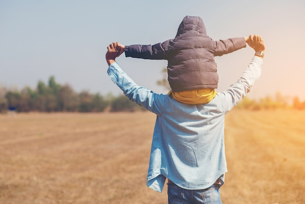 Small boy is sitting on his father's shoulders and pretending a plane Premium Photo