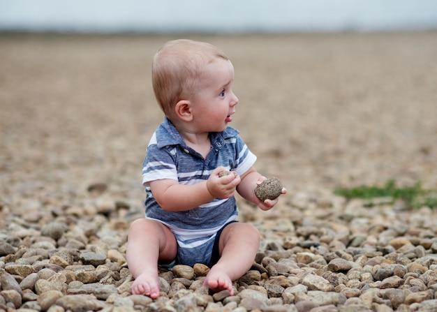 Маленький мальчик играет с камнями на берегу моря Premium Фотографии