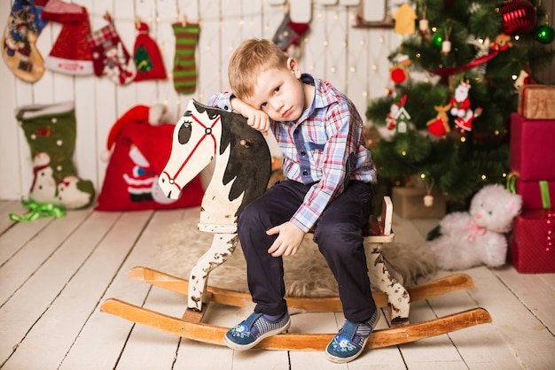 Small boy riding wooden rocking horse in front of christmas tree Premium Photo