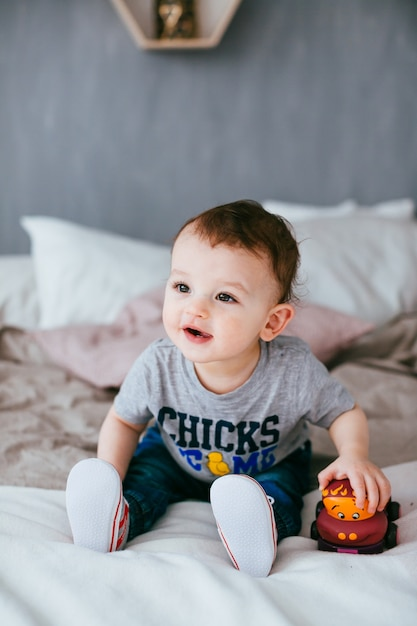 The small boy with car sitting on the bed Free Photo