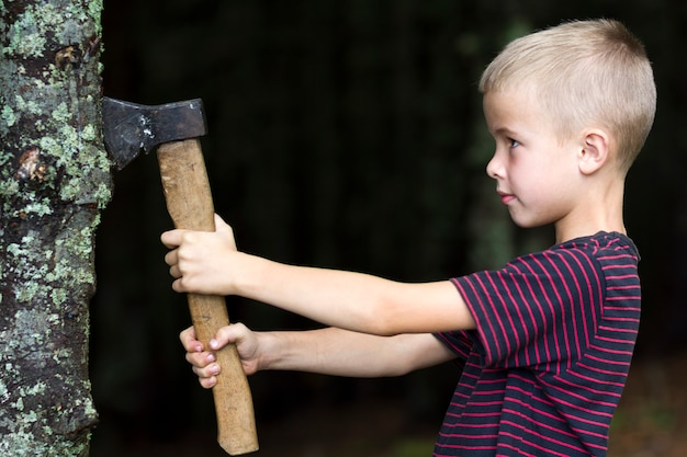 Small boy with heavy old iron axe cutting tree trump in forest on summer day. outdoor activities and physical labor. Premium Photo