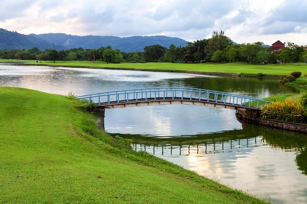 ゴルフ場の緑の芝生とラグーンの小さな橋。 Premium写真