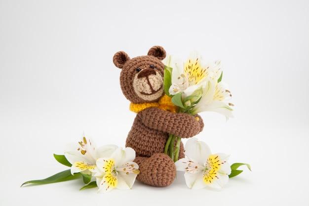 Small brown bear with white flowers, knitted toy, handmade. amigurumi. Premium Photo