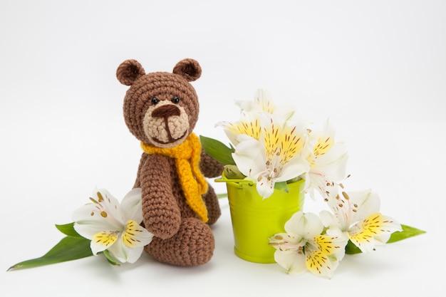 Small brown bear with white flowers , knitted toy, handmade. amigurumi. Premium Photo