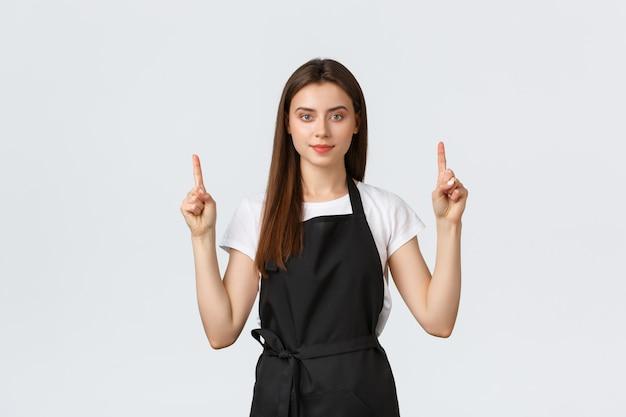 Концепция малого бизнеса, работников и кофейни. уверенно красивая бариста в черном фартуке, указывая пальцами вверх. сотрудник кафе показывает рекламу. веселая продавщица рекомендует специальную акцию Premium Фотографии
