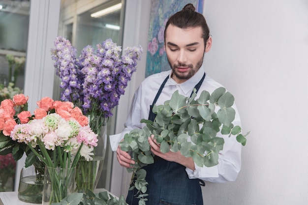 Small business. male florist in flower shop.  making decorations and arrangements Free Photo