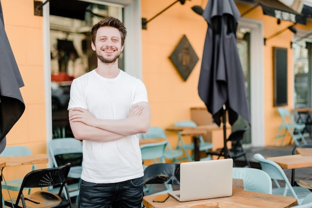 Small business owner outside his cafe with laptop Premium Photo