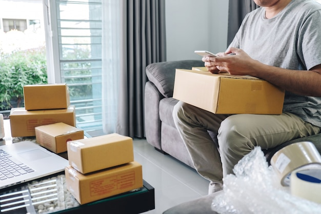 Small business parcel for shipment to client at home, young entrepreneur sme freelance man working online business by using smart phone with making on purchase order and preparing package product Premium Photo