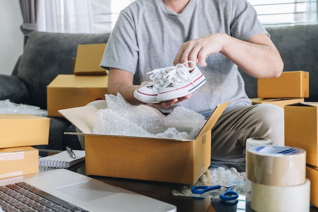 Small business parcel for shipment to client, young entrepreneur sme freelance man working with packaging shoe into box delivery online market on purchase order and preparing package product at home Premium Photo