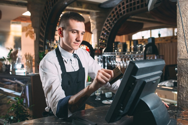 Small business, people and service concept - happy man or waiter in apron at counter with cashbox working at bar or coffee shop Premium Photo