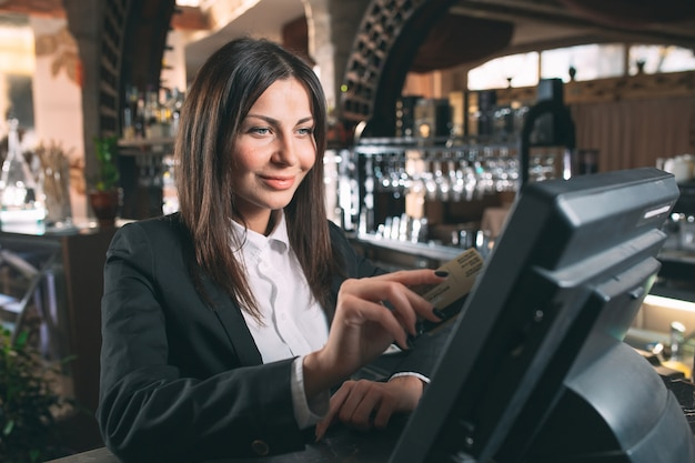 Small business, people and service concept - happy woman or waiter or manager in apron at counter with cashbox working at bar or coffee shop Premium Photo