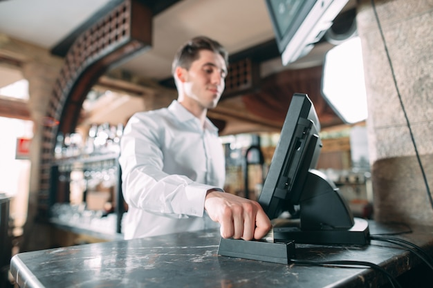 Small business, people and service  - happy man or waiter in apron at counter with cashbox working at bar or coffee shop. Premium Photo