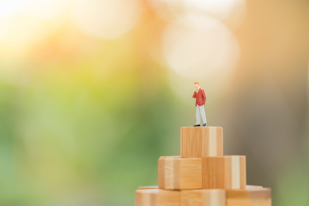 Small businessman figure standing on top wooden block. Premium Photo