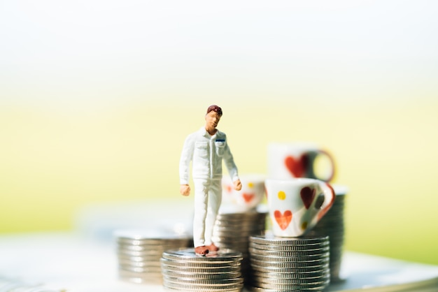 Small businessmen standing on stack of coins with city backgrounds. Premium Photo