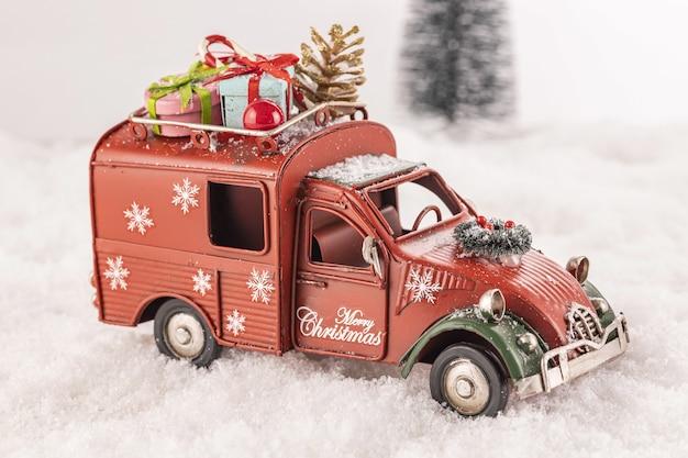 Piccola automobile giocattolo decorata con ornamenti sulla neve artificiale con un albero di natale in background Foto Gratuite