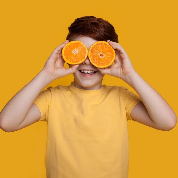 Маленький кавказский рыжий мальчик закрывает глаза апельсинами, позирует в футболке на желтой стене со свободным пространством Premium Фотографии