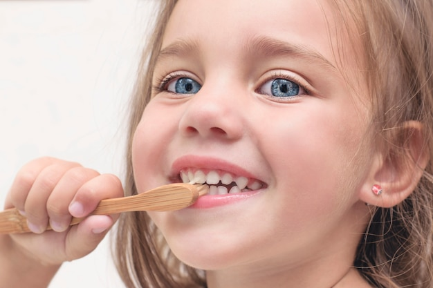 Premium Photo | Small child brushes teeth with a bamboo toothbrush