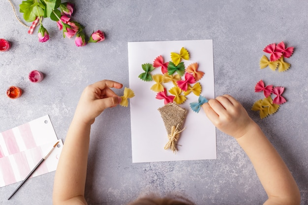 Small child doing a bouquet of flowers out of colored paper and colored pasta. Premium Photo