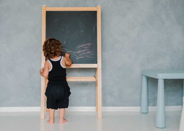 Small child draws with chalk on a black chalk board at home in the nursery against a gray wall. Premium Photo
