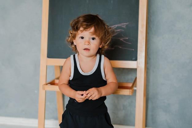 Маленький ребенок рисует мелом на черном меловой доске дома в питомнике на фоне серой стены. Premium Фотографии