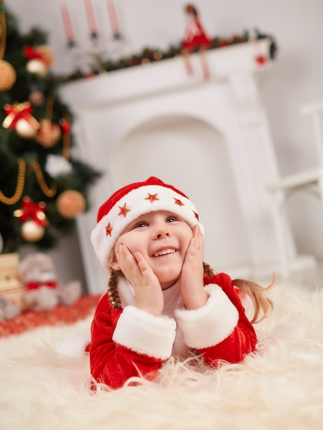 Small child dressed as santa claus with hands on face Free Photo