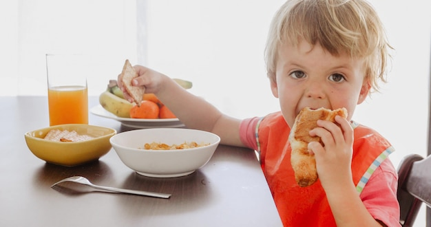 Small child eating croissant at breakfast Premium Photo