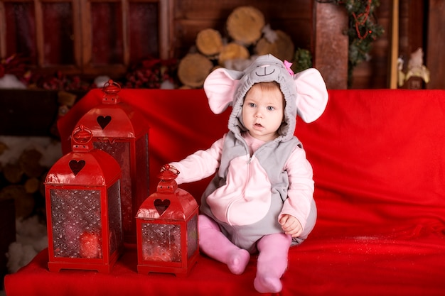 Small child (girl) in festive suit of mouse (rat) sits near flashlights and christmas decorations Premium Photo