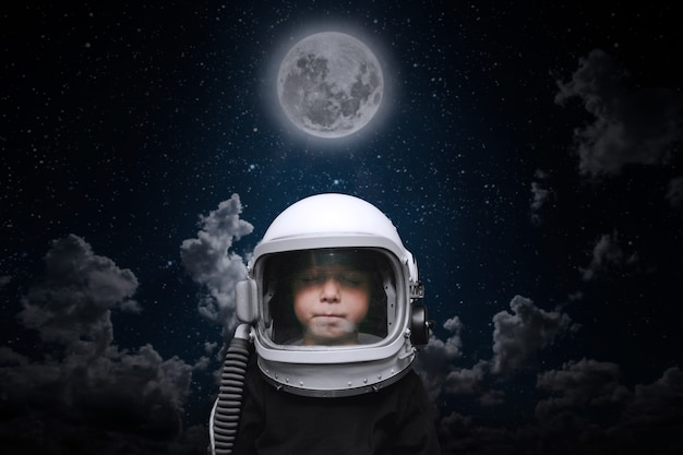 A small child imagines himself to be an astronaut in an astronaut's helmet. elements of this image furnished by nasa Premium Photo