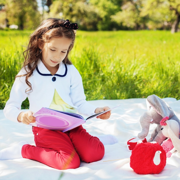 A small child is reading an interesting book with fairy tales. Premium Photo